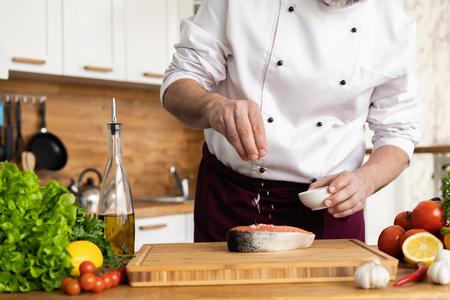 El chef prepara pescado fresco, salmón, trucha, espolvorea con sal marina y verduras. Foto horizontal. Concepto de cocina sana y vegana, comida limpia, restaurantes, hostelería. Foto de archivo