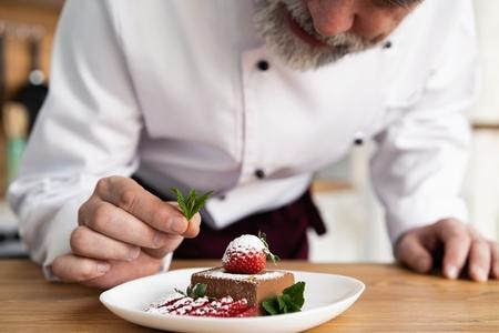 Bliska dekoracji cukiernik pyszne danie deserowe, służąc klientom w piekarni, przyozdobiając talerz deserowy w komercyjnej kuchni.