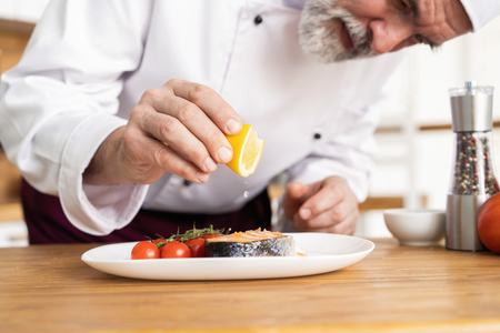 Chef with diligence finishing dish on plate, fish with vegetables Stock Photo - 124623622