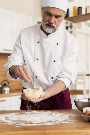 Making dough by male hands at bakery