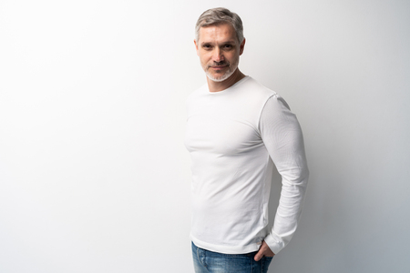 Cheerful man of middle age against white background, wearing jeans and white T-shirt, mid shot. 스톡 콘텐츠