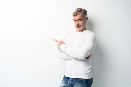 Schöner älterer Mann mittleren Alters, der mit der Handfläche auf weißem Hintergrund in die Kamera schaut und zeigt. Standard-Bild