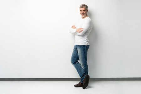 Full body portrait of relaxed mature man standing with arms crossed over white background.