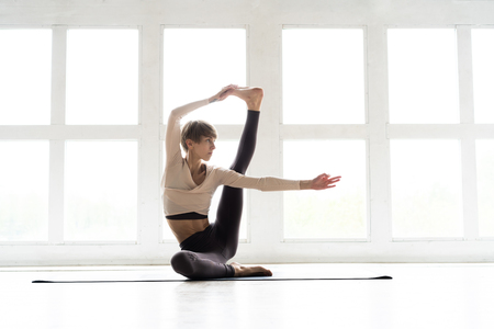 Young attractive smiling woman practicing yoga, sitting in One Legged King Pigeon exercise, Eka Pada Rajakapotasana pose, working out, wearing sportswear, brown pants, bra, indoor full length, home.