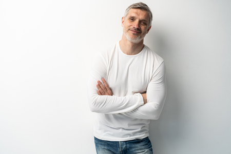 Cheerful man of middle age against white background, wearing jeans and white T-shirt, mid shot. Stock fotó
