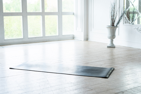 Unrolled yoga mat lying in empty light fitness studio on wooden floor, unfolded sport equipment prepared for training, modern pilates loft room ready for workout session. Healthy life concept. Stockfoto