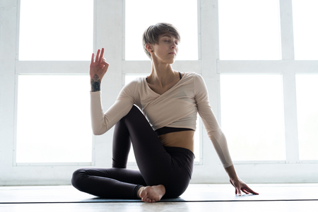 Young attractive woman practicing yoga, sitting in Ardha Matsyendrasana exercise, Half lord of the fishes pose, working out, wearing sportswear. Stock Photo