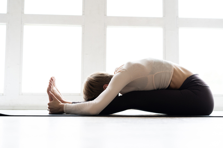 Young woman practicing yoga, sitting in Seated forward bend exercise, paschimottanasana pose, working out, wearing sportswear, home interior background.