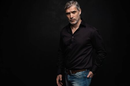 Middle-aged good looking man posing in front of a black background with copy space.
