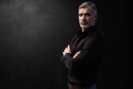Hombre guapo de mediana edad posando delante de un fondo negro con espacio de copia.