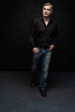 Full body portrait of middle-aged good looking man posing in front of a black background with copy space.