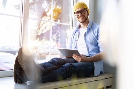 Man using Tablet for Work and Browsing Information, Young creative manager sitting by the window.