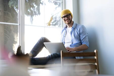 Young businessman working on modern loft office. Man sitting by the window, using contemporary notebook.