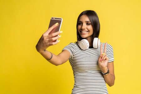Portrait of a pretty girl taking a selfie isolated over color background.