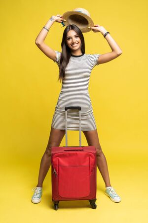 Woman traveler with suitcase on color background. Фото со стока