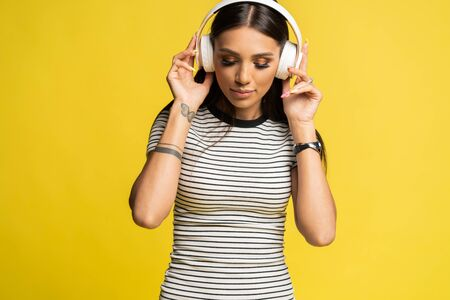 Gorgeous brunette lady listening music in headphones and singing on yellow background.