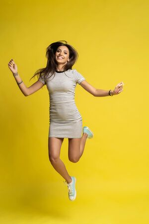 Full length photo of charming young woman in casual wear jumping over color background.