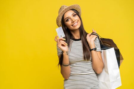 Image of smiling brunette young woman standing isolated over yellow background looking camera holding shopping bags and credit card Stockfoto