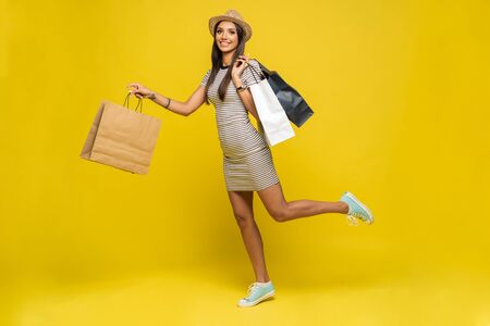 Full length portrait of a happy pretty girl holding shopping bags while running and looking at camera isolated over color background.
