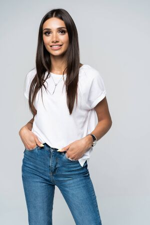 Pretty smiling joyfully female with fair hair, dressed casually, looking with satisfaction at camera, being happy. Studio shot of good-looking beautiful woman isolated against blank studio wall.