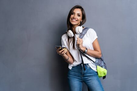 Young beautiful woman with smart phone. Smiling student going on a travel. Isolated on gray background. 스톡 콘텐츠