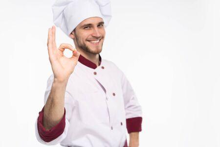 Cocinero feliz profesional positivo del hombre que muestra la muestra aceptable sabrosa aislada en el fondo blanco.