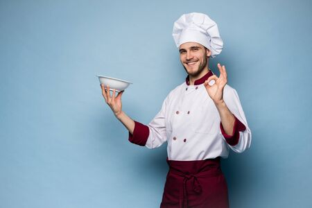 Positive professional happy man chef showing tasty ok sign isolated on light blue. Stockfoto - 125897813