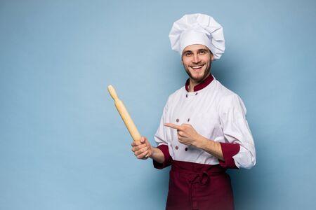 Retrato de cocinero dentudo positivo cocinero en boina, traje blanco con herramientas en brazos cruzados mirando a cámara.