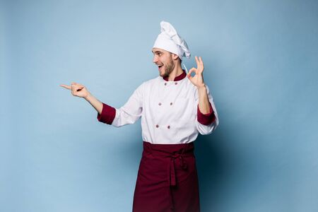 Positive professional happy man chef showing tasty ok sign isolated on light blue.