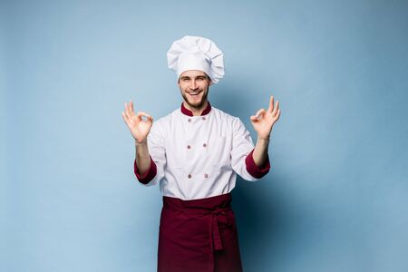 Positive professional happy man chef showing tasty ok sign isolated on light blue. Stockfoto - 125898046