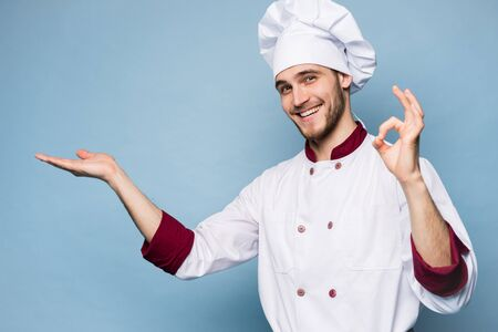 Positive professional happy man chef showing tasty ok sign isolated on light blue. Stockfoto - 125898053
