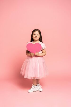Laughing fashion little girl in tulle dress holding red paper heart and smiling to camera isolated on pink background.