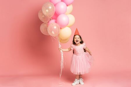 Happy celebration of birthday party with flying balloons of charming cute little girl in tulle dress smiling to camera isolated on pink background. Charming smile, expressing happiness