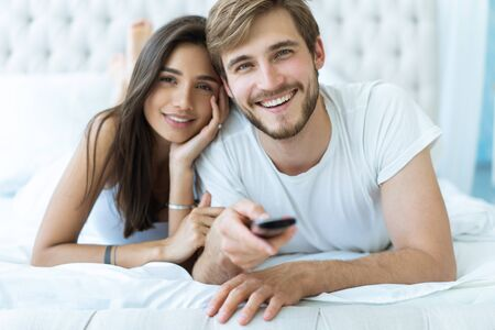 happy couple with remote lying in bed at home and watching tv.