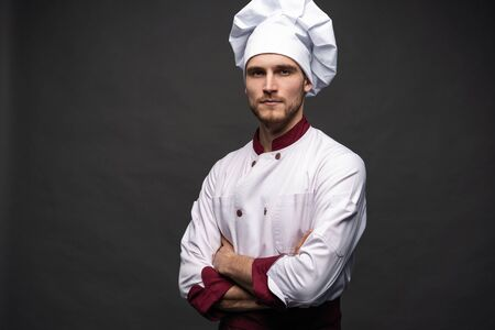 Young male chef isolated on a black background.