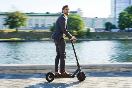 Hombre de negocios joven en un traje que monta un scooter eléctrico en una reunión de negocios. Foto de archivo