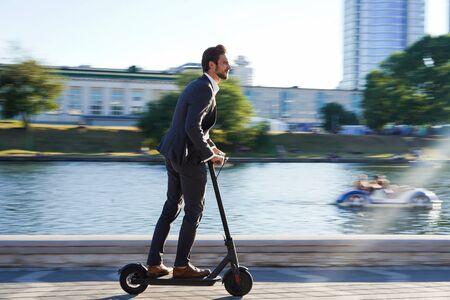 Giovane uomo d'affari in giacca e cravatta in sella a uno scooter elettrico durante una riunione d'affari.