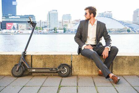 Giovane uomo moderno utilizzando scooter elettrico sulla strada della città. Concetto di trasporto moderno ed ecologico.