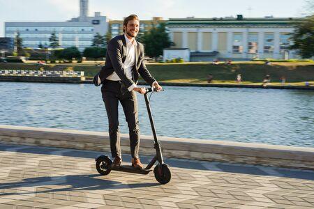 Hombre de negocios joven en un traje que monta un scooter eléctrico en una reunión de negocios.