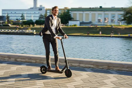Young business man in a suit riding an electric scooter on a business meeting. Reklamní fotografie - 127501219