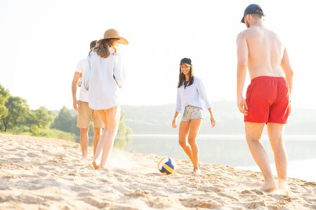 Group of young people playing with ball at the beach. Young friends enjoying summer holidays on a sandy beach Stok Fotoğraf