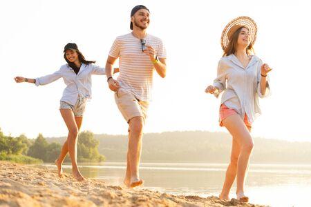 Group of friends having fun running down the beach
