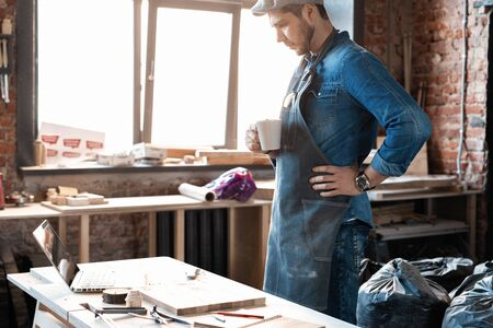 Young joiner work at his workstation. Successful handsome businessman with stylish cap work in carpentry Stock fotó