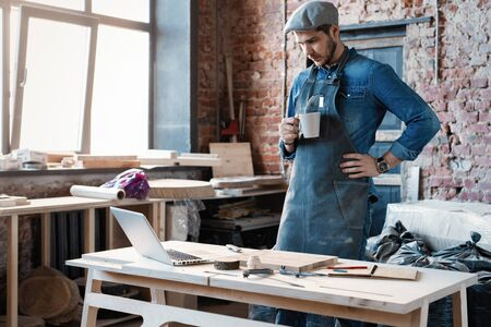 Young joiner work at his workstation. Successful handsome businessman with stylish cap work in carpentry