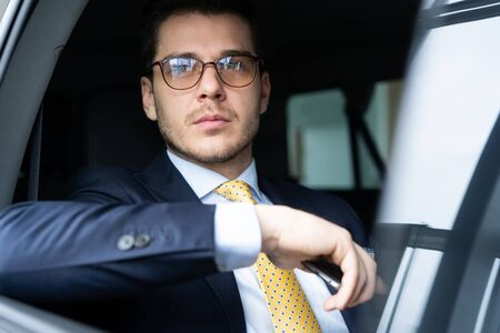 Young businessman sitting on back seat of the car, while his chauffeur is driving automobile. Reklamní fotografie