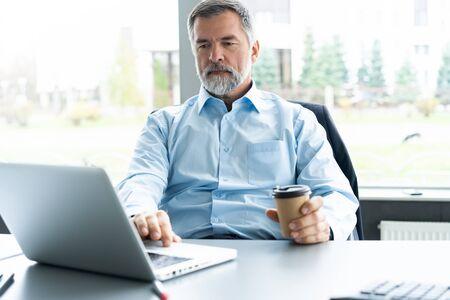 Senior Geschäftsmann arbeitet an Laptop-Computer Standard-Bild