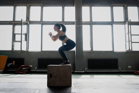 Fit young woman box jumping at a crossfit style gym. Female athlete is performing box jumps at gym.