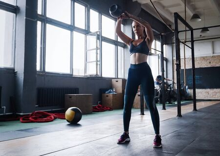 Young fitness female exercise with kettle bell. Caucasian woman doing crossfit workout at gym. 스톡 콘텐츠