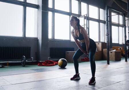 Junge Fitness-Frauenübung mit Wasserkocher Glocke. Kaukasische Frau beim Crossfit-Training im Fitnessstudio.