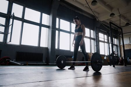 Attractive strong muscular female bodybuilder doing heavy duty squats lifting barbell at the crossfit gym